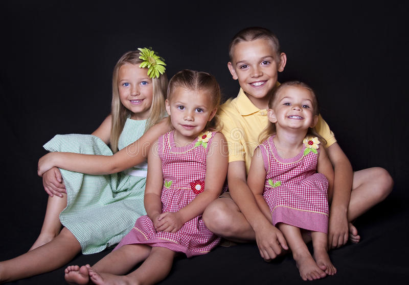 Beautiful Smiling children. Portrait of cute, smiling children on a black background stock photography