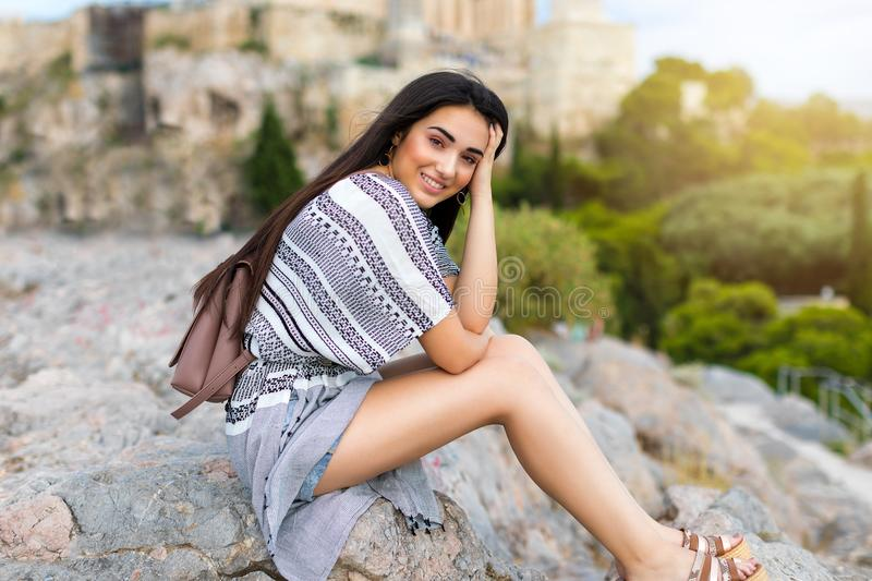 Beautiful city traveler girl sits on rocks in front of the Acropolis of Athens royalty free stock photo