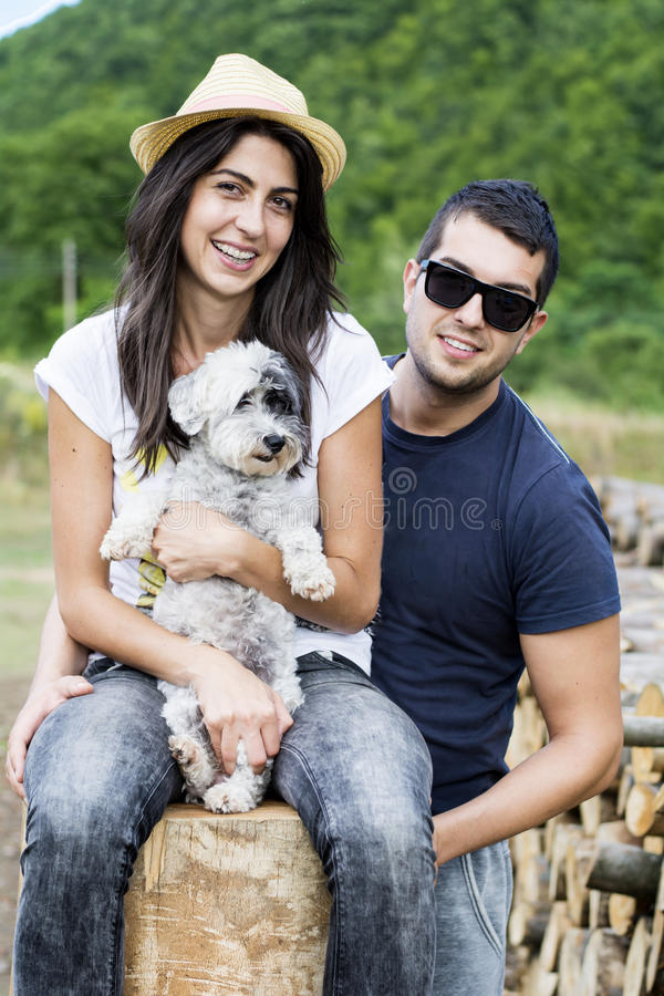 Beautiful smiling couple hugging their white dog outdoor royalty free stock photos