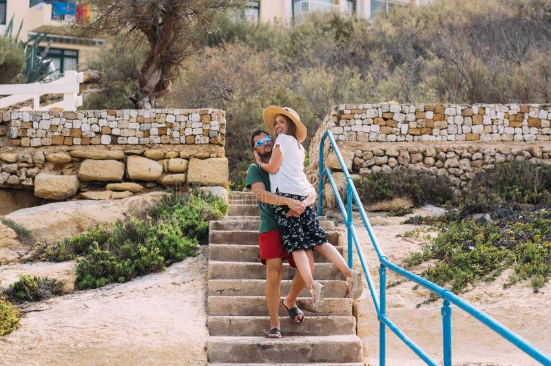 Beautiful smiling couple, men holds women on hands. Gozo, Malta stock photo