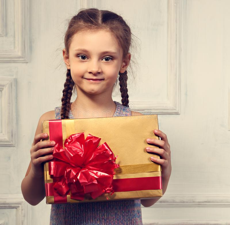 Beautiful smiling cute girl holding the gold box with gift with royalty free stock photography