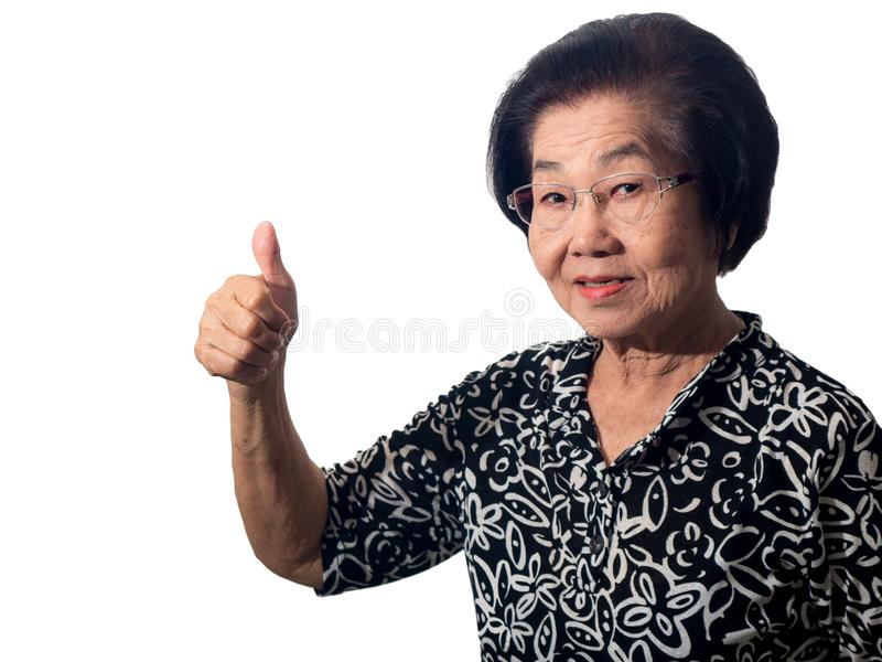 Beautiful smiling elderly asian woman raises her thumb up standing on white background. Gesture everything is okay stock image