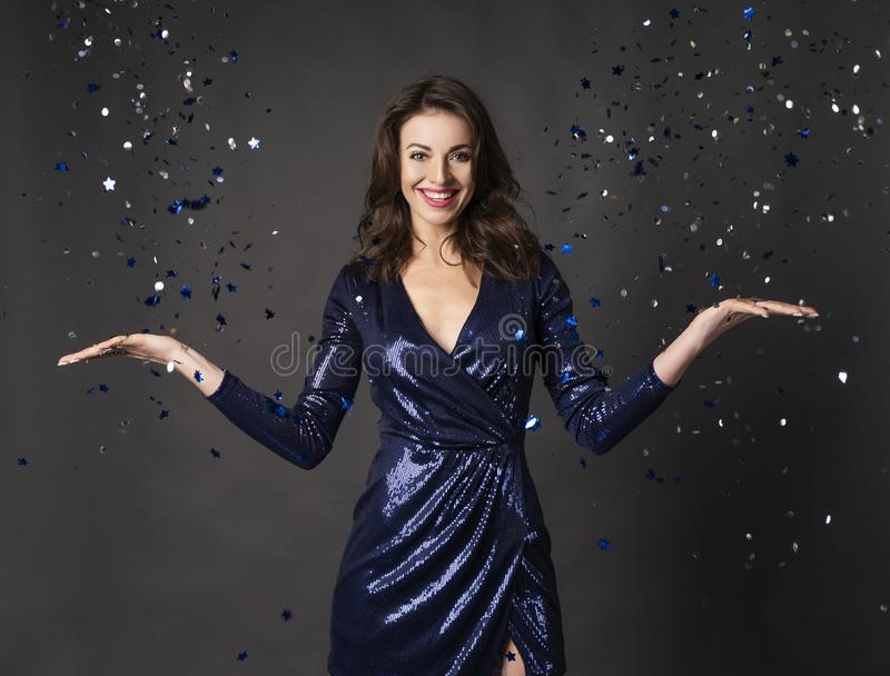 Beautiful, smiling, elegant brunette woman, dressed in a brilliant blue dress throws festive glitter and confetti into the air. Gray background. Copy space royalty free stock photo