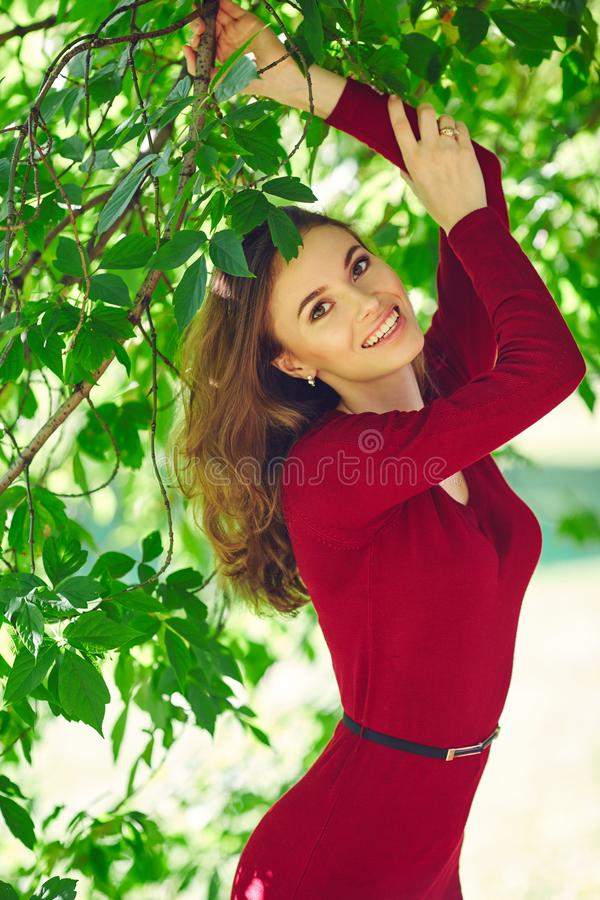 Beautiful smiling face of young woman in a red dress. Outdoor portrait stock photography