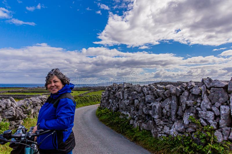 Beautiful and smiling female cyclist pausing on a road between stone fences on Inis Oirr Island. Field with limestone fences and the sea in the background royalty free stock photos