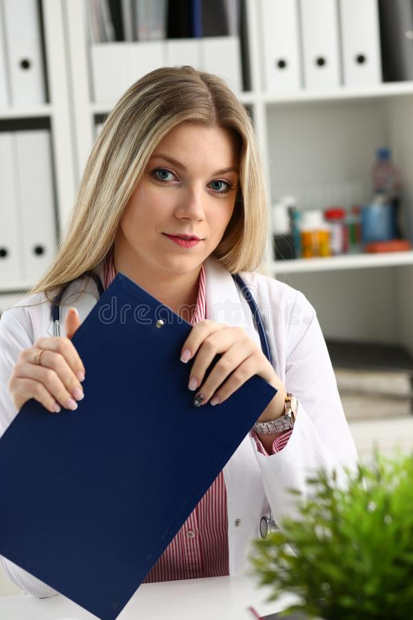 Beautiful smiling female doctor hold clipboard. Pad and fill something with silver pen. Physical illness prevention prescribe remedy ward round therapeutist royalty free stock photos