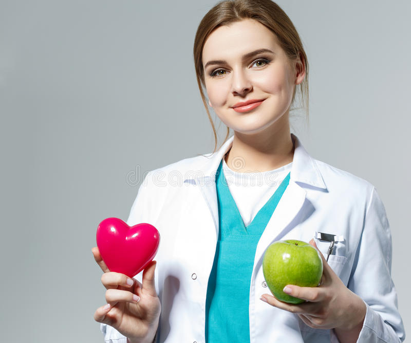 Beautiful smiling female doctor holding red heart and green apple royalty free stock photography