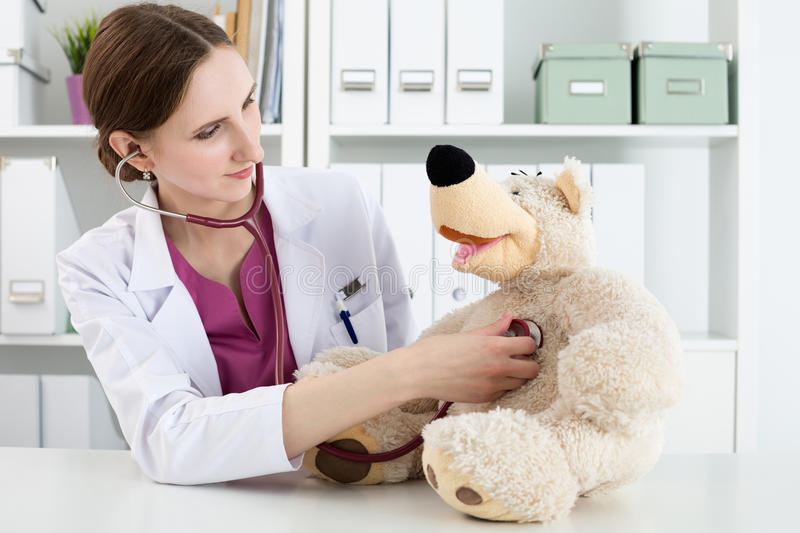 Beautiful smiling female doctor in white coat examine teddy bear. Family doctor examination. Beautiful smiling female doctor in white coat examine teddy bear royalty free stock photography