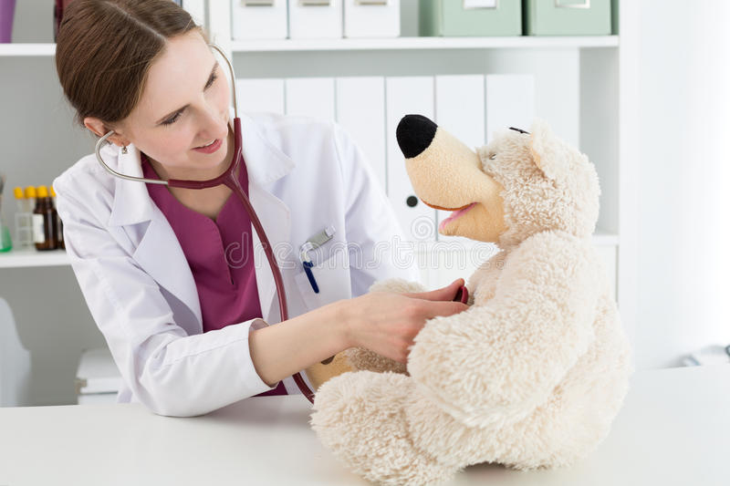 Beautiful smiling female doctor in white coat examine teddy bear. Family doctor examination. Beautiful smiling female doctor in white coat examine teddy bear stock images