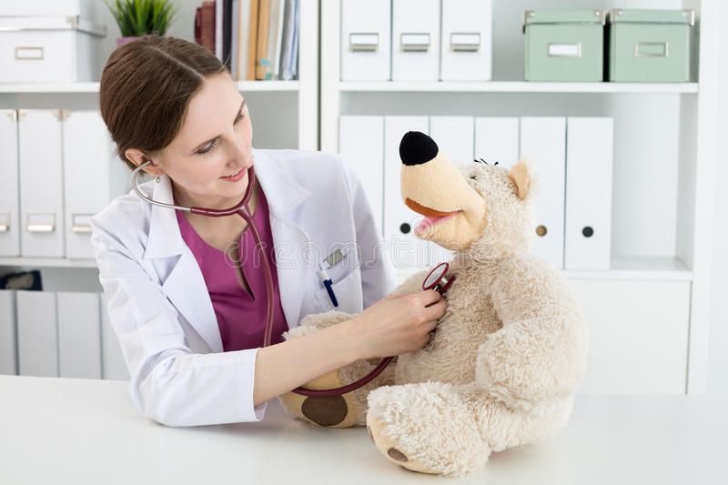 Beautiful smiling female doctor in white coat examine teddy bear. Family doctor examination. Beautiful smiling female doctor in white coat examine teddy bear royalty free stock image