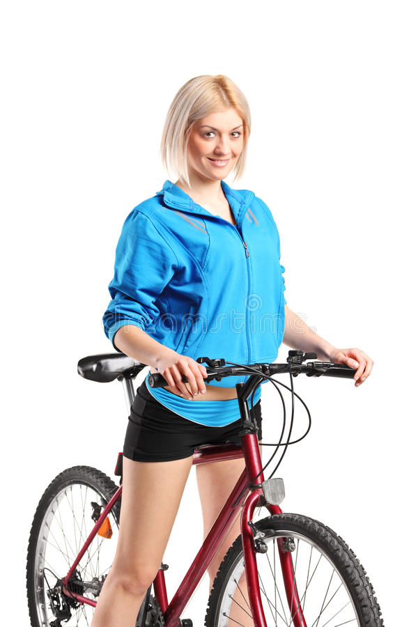 Beautiful smiling female posing next to a bicycle stock images