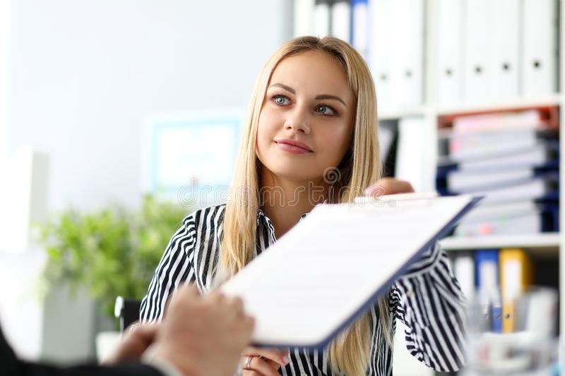Beautiful smiling female real estate agent offering male visitor document to sign royalty free stock photo
