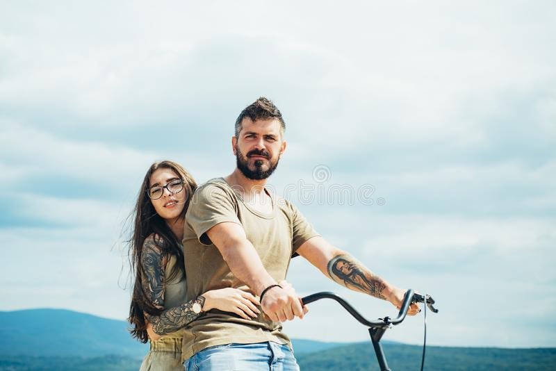 Beautiful smiling girl and bearded hipster man is riding the bicycle in the park. Couple riding bicycle on sunny day royalty free stock images