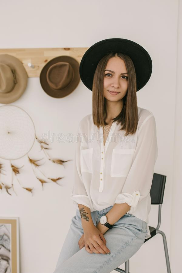 A beautiful smiling girl in a black hat is looking into the camera. Summer beauty. Romantic shot. Hats on the background stock photography