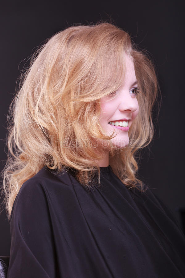 Beautiful smiling girl with blond wavy hair by hairdresser in beauty salon royalty free stock images
