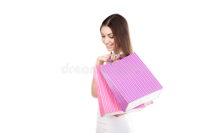 Beautiful smiling girl carrying colorful shopping bags. Smiling female holding colored shopping bags, copy space, isolated on white background. Concepts: sales stock photos
