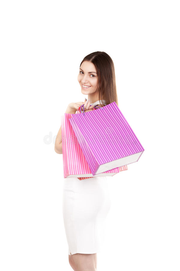 Beautiful smiling girl carrying colorful shopping bags. Smiling female holding colorful shopping bags, isolated on white background. Concepts: sales, rest royalty free stock photos