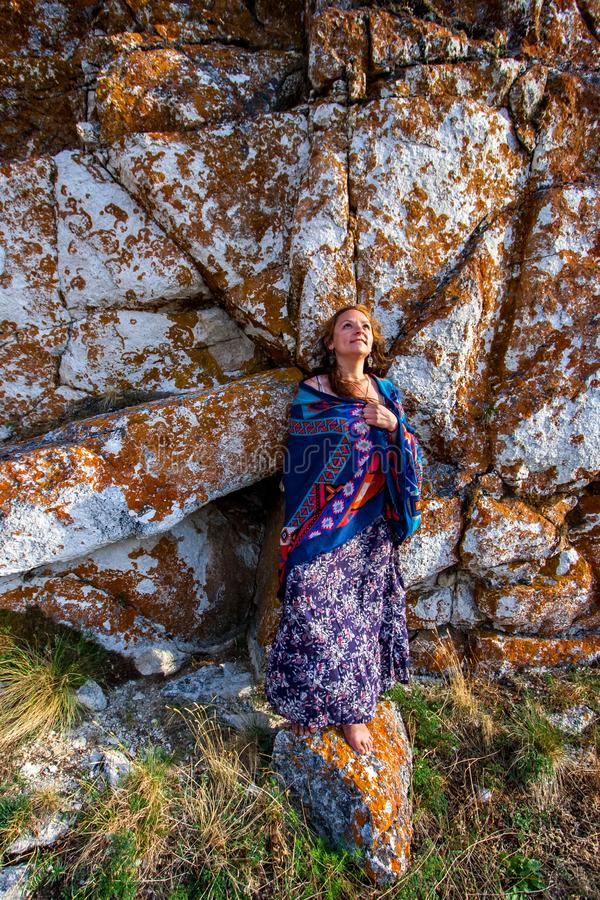A beautiful smiling girl in a dress and shawl stands against a stone wall of white large stones covered with red moss. royalty free stock photo