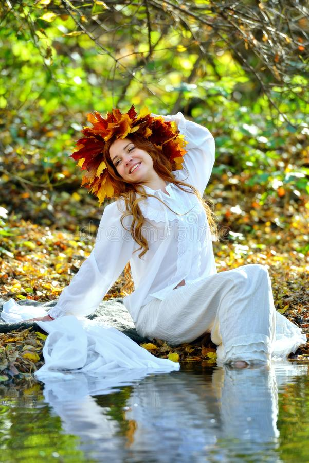 Beautiful smiling girl dressed in white, wearing a wreath of yellow leaves, sitting and posing by the water on a Sunny autumn day royalty free stock photo