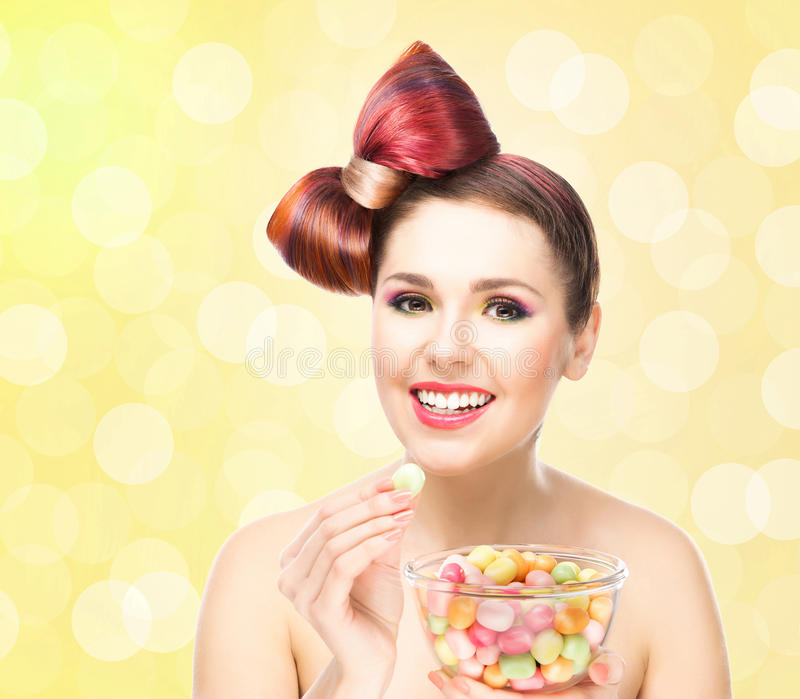 Beautiful smiling girl eating sweets from a bowl on blink background.  royalty free stock photography