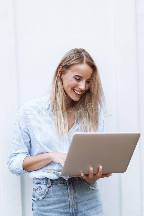 Beautiful smiling girl holding laptop computer stock image