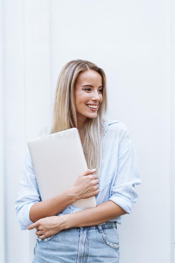 Beautiful smiling girl holding laptop computer stock images