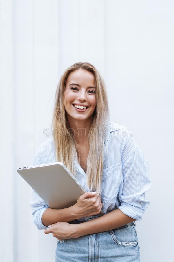 Beautiful smiling girl holding laptop computer stock photos