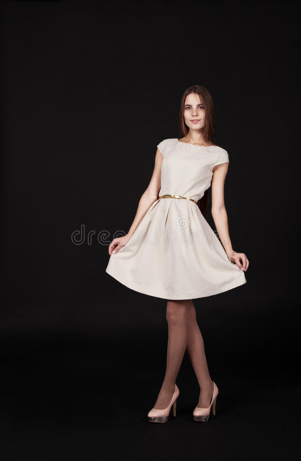 Beautiful smiling girl in a light dress posing standing royalty free stock image