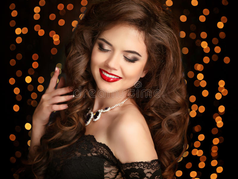 Beautiful smiling girl. Makeup. Fashion jewelry. Hairstyle. Happy brunette with red lips and long curly hair isolated on party l stock image