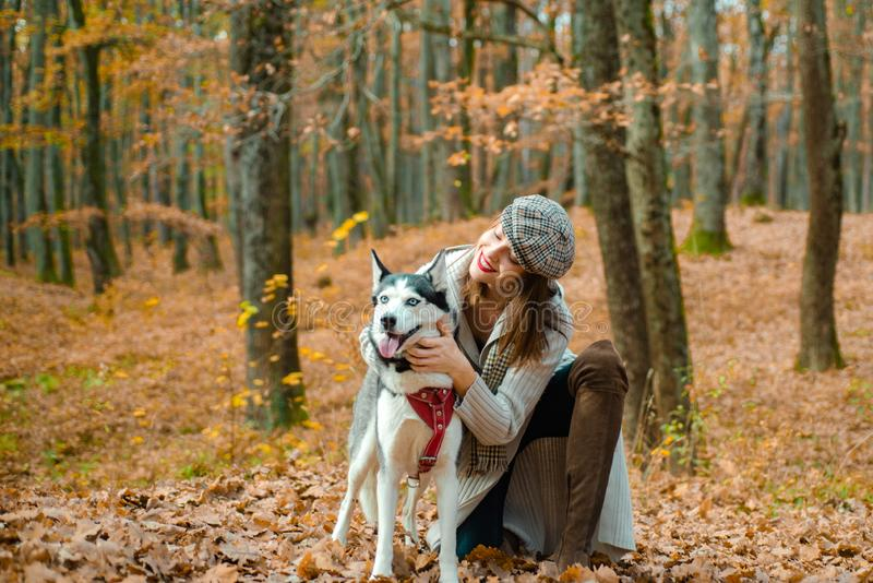 Beautiful smiling girl petting her husky dog. Woman with her dog chose a great place to stroll, because the paints of royalty free stock photos