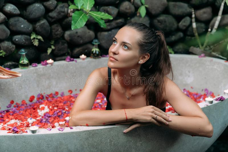 Beautiful smiling girl relaxing in bath with rose petals and tropical flowers outdoor at spa day stock photography