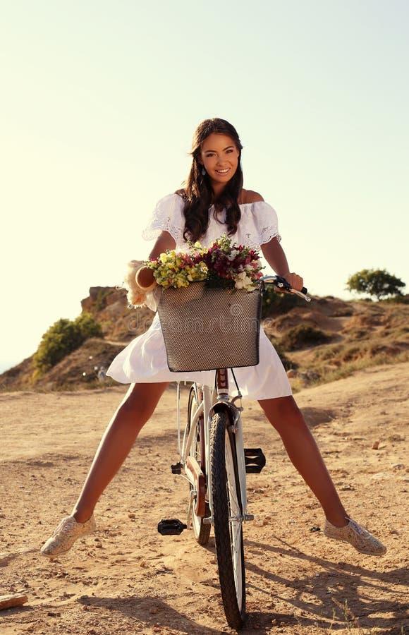 Beautiful smiling girl riding a bicycle along the sea coast stock photo