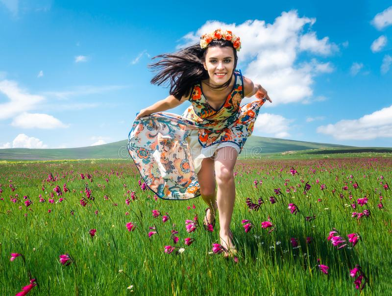 Beautiful smiling girl running in flowering meadom in colorful dress. Attractive brunette woman in wreath running along royalty free stock photos