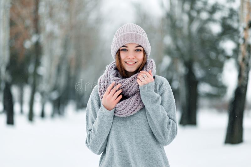 Beautiful smiling girl stands on the road in a hat and sweater in the winter stock photography
