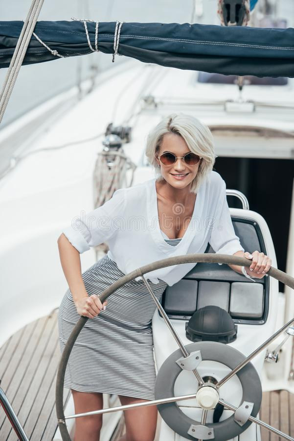 beautiful smiling girl in sunglasses standing at steering wheel stock image