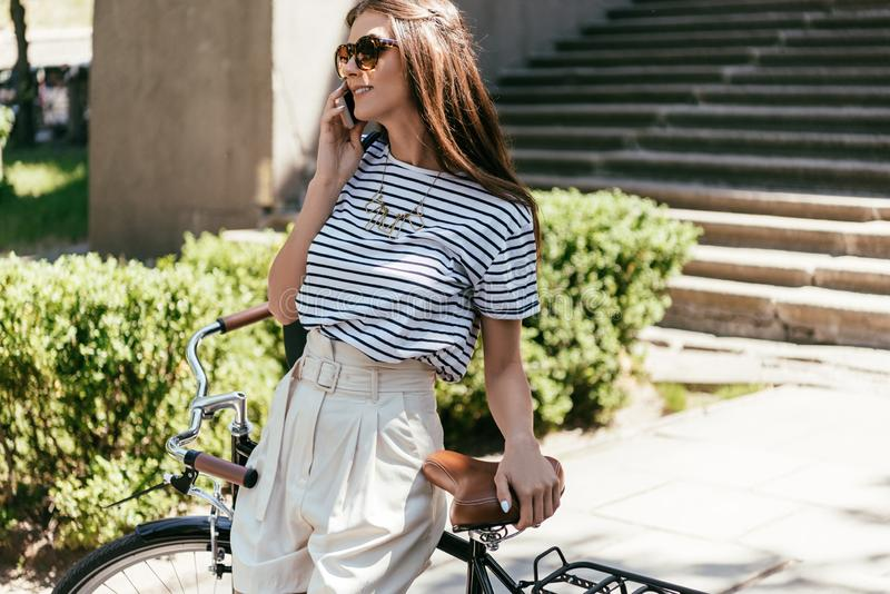 beautiful smiling girl in sunglasses talking by smartphone and looking away while standing with bike royalty free stock photography