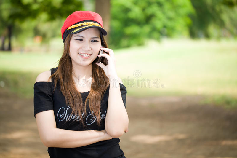 Beautiful smiling girl talks on cellular telephone outdoors. Beautiful smiling girl and red hat talks on cellular telephone outdoors royalty free stock images