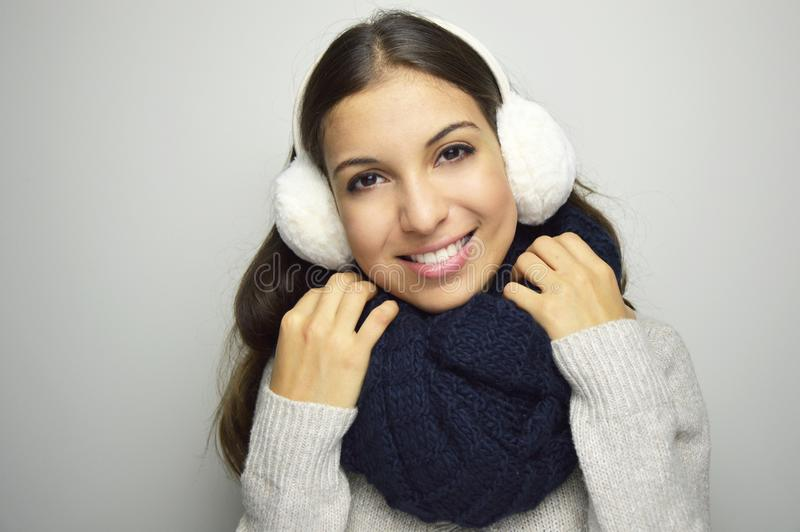 Beautiful smiling girl in warm clothing close up portrait. Young woman being cold wearing earmuffs, scraf and sweater. royalty free stock photo