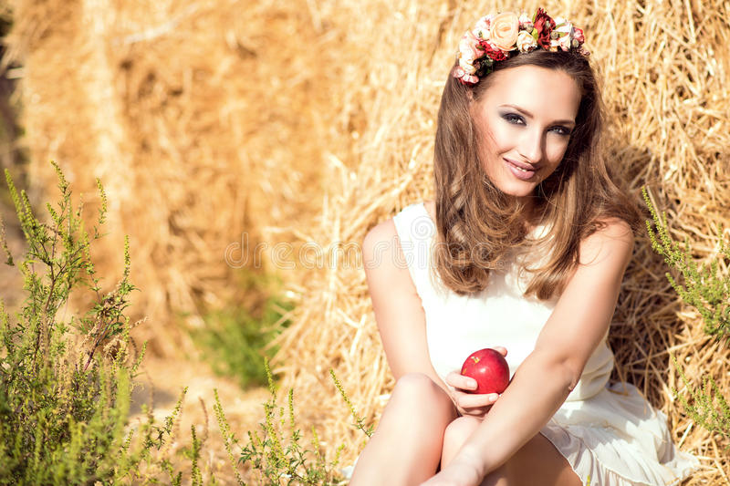 Beautiful smiling girl wearing white summer dress and floral head wreath sitting at the haystacks and holding a red apple royalty free stock photo