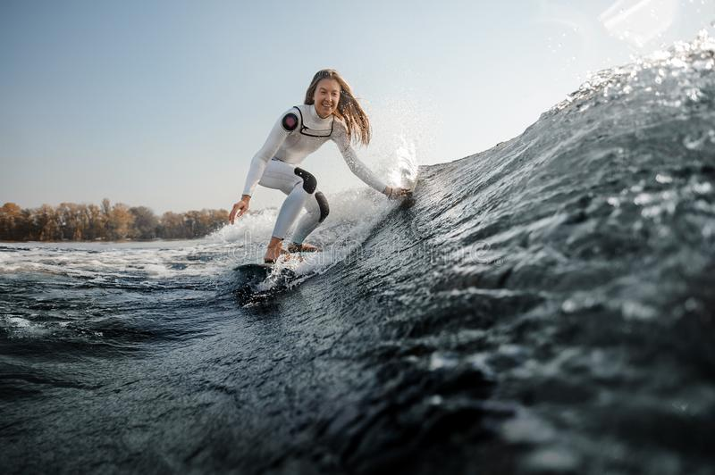 Smiling girl riding on the wakeboard on the bending knees royalty free stock images