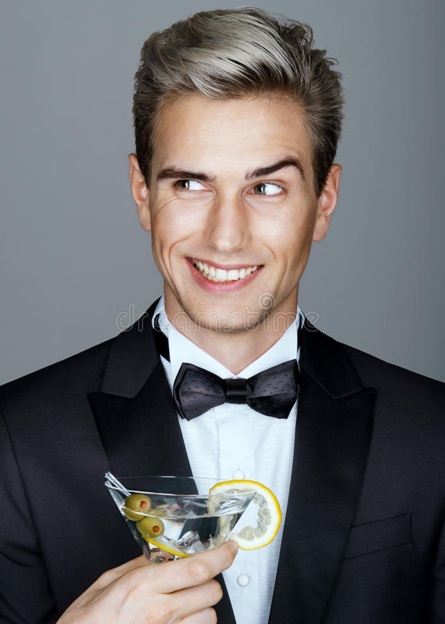 Beautiful smiling handsome man in black suit with glass of martini royalty free stock photos