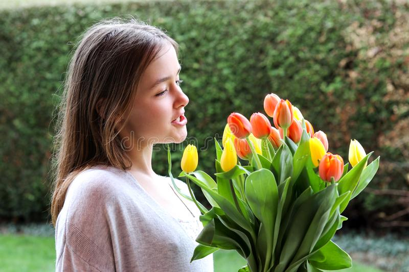 Beautiful smiling happy tween girl holding big bouquet of bright yellow and orange tulips talking to them. Outdoors in garden at warm spring day. Spring flowers royalty free stock image
