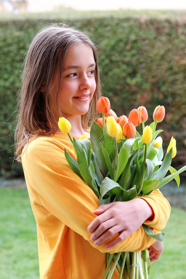 Beautiful smiling happy tween girl in yellow sweater holding and hugging big bouquet of bright orange tulips outdoors. In garden at warm spring day. Spring stock images