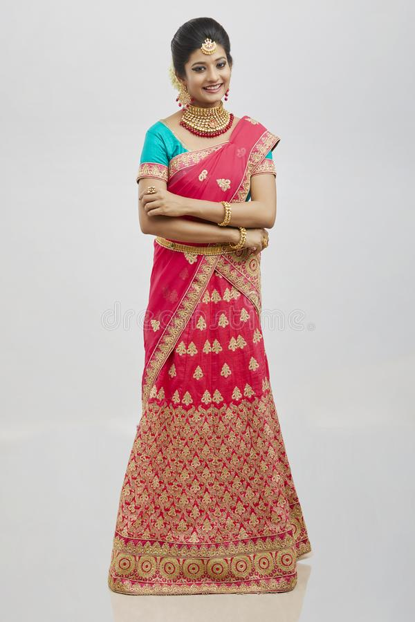 Beautiful smiling Indian bride with jewelry in studio shot. stock photo