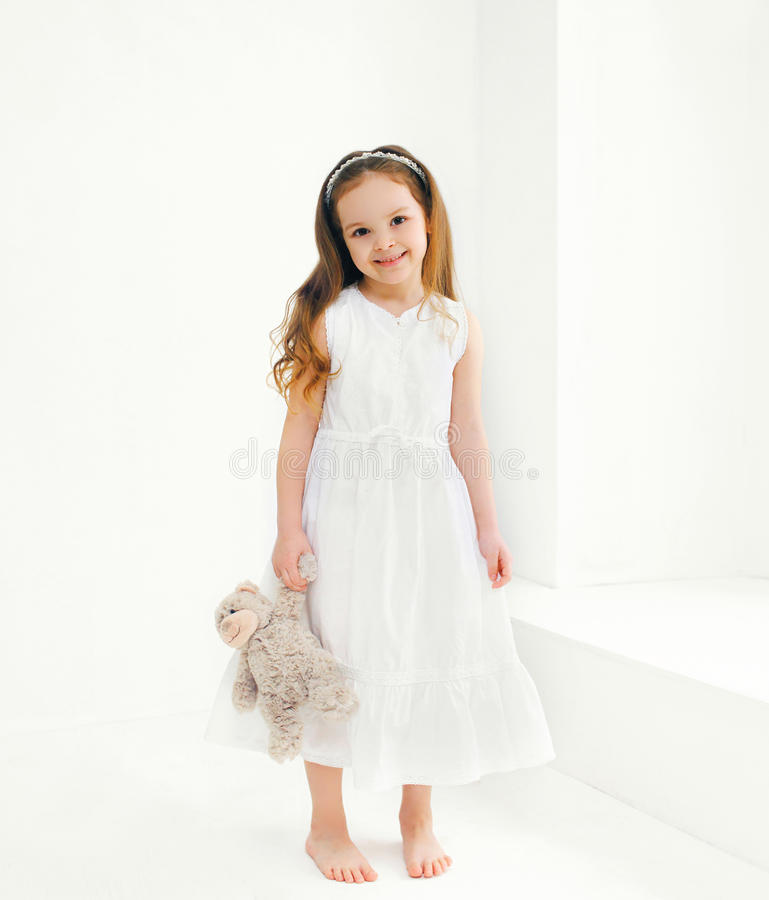 Beautiful smiling little girl child with teddy bear toy at home royalty free stock photography