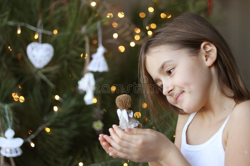 Beautiful smiling little girl decorating Christmas tree and holding angel doll in her hands. Lokking at her with tenderness. New Year magic. Natural bokeh royalty free stock photo
