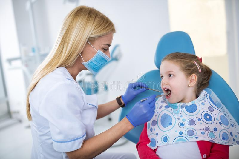 Beautiful smiling little girl in dental office stock photo