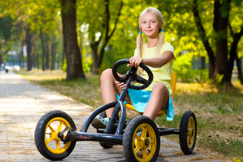 Beautiful smiling little girl riding toy car in stock images