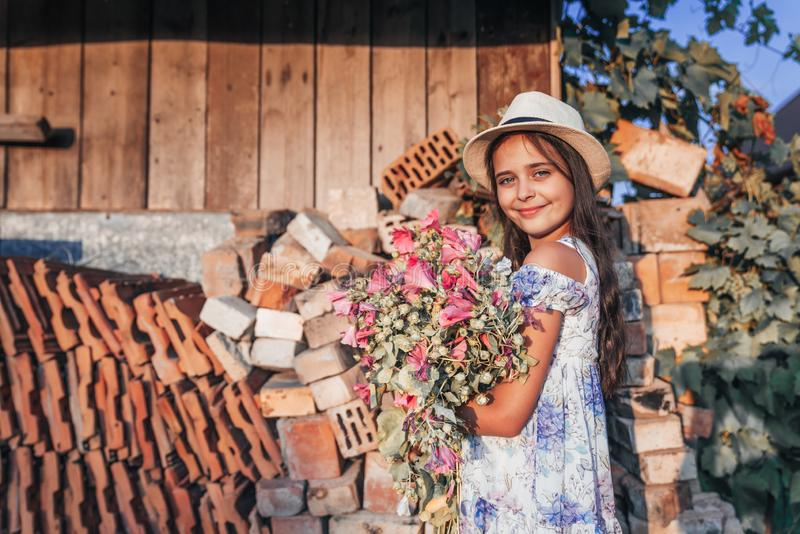 Beautiful smiling little girl in white hat with healthy skin looking at the camera and holding a large bouquet of pink royalty free stock images