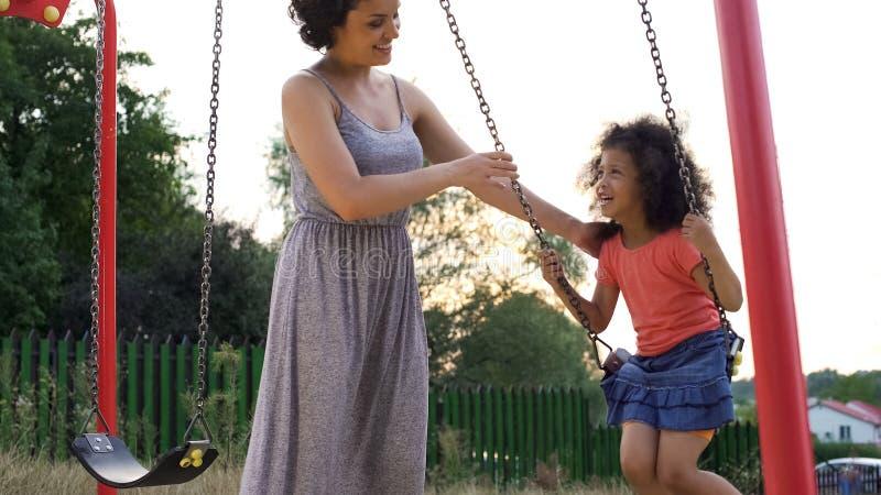 Beautiful smiling mother in grey dress swinging her favorite giggling daughter royalty free stock photos